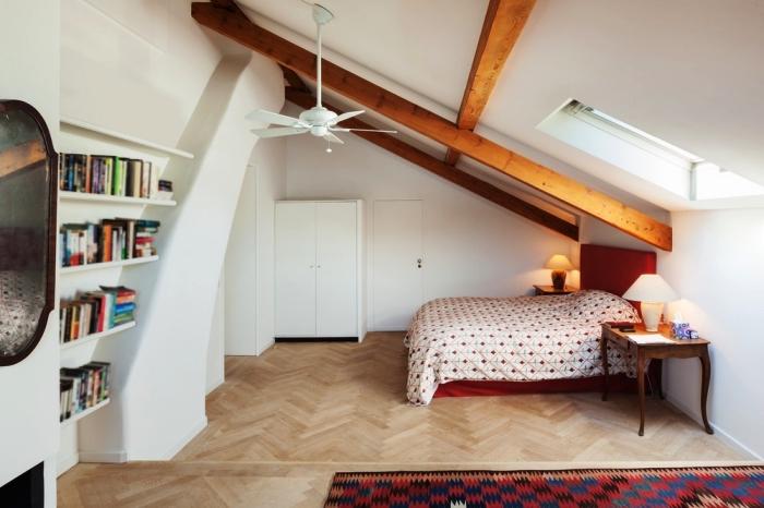 l'aménagement d'une suite parentale mansardée avec lit posé en sous-pente et des poutres apparentes qui structurent l'espace