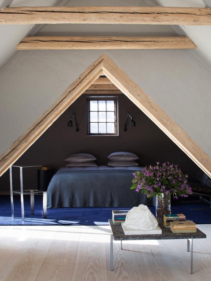 chambre à coucher sous pente avec lit mis en valeur grâce au mur peint couleur taupe et à la charpente apparente