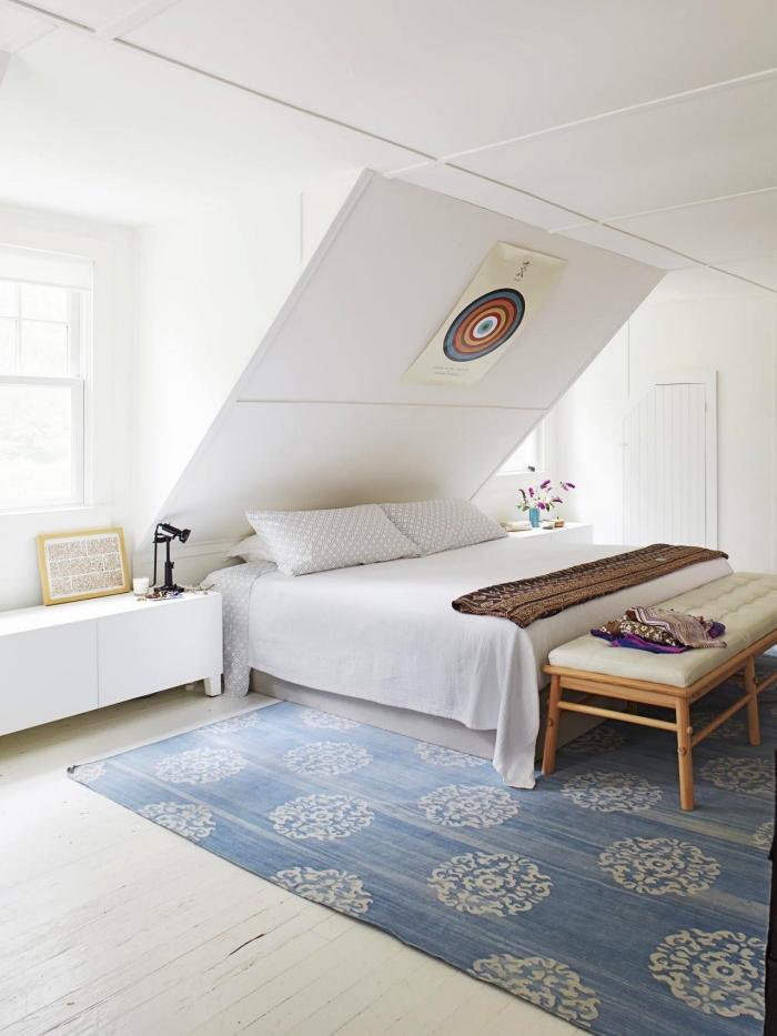 une chambre parentale blanche monochrome aménagée sous les combles avec un lit posé en sous-pente