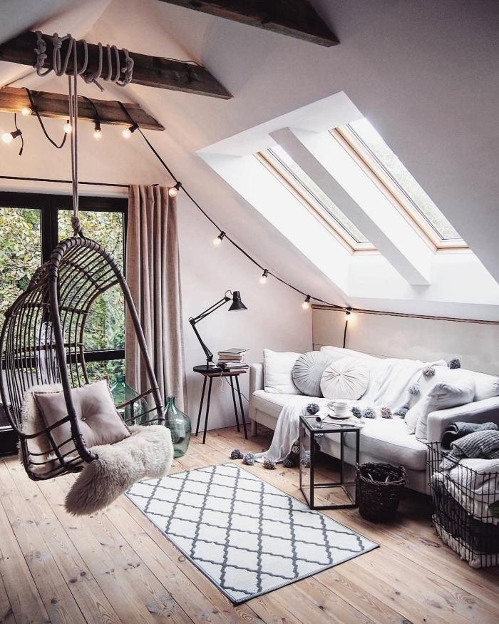 décoration cocooning dans une chambre sous comble de style scandinave avec canapé blanc en dessous des fenêtres de toit et une balançoire suspendue à la poutre de bois