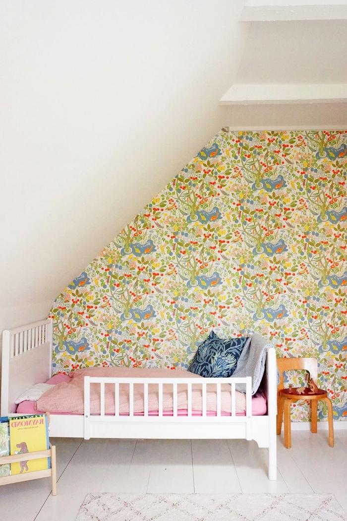 une chambre d'enfant vintage aménagée sous les combles avec petit lit blanc posé en sous-pente contre le mur d'accent en papier peint vintage floral