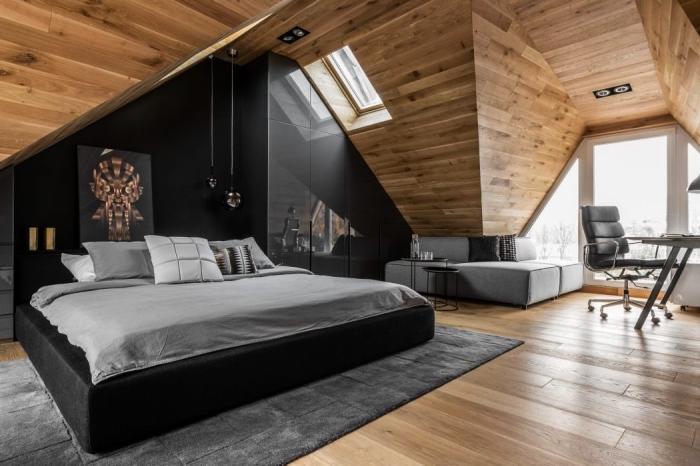 une suite parentale de large surface aménagée sous les combles avec dressing sous pente noir design et un canapé d'angle gris