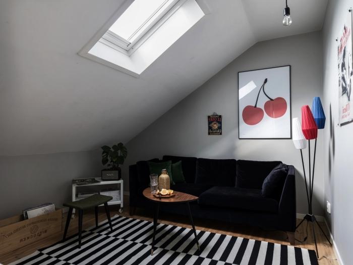 petit salon mansardé de style vintage scandinave avec canapé en velours couleur bleu nuit et un petit meuble sous pente