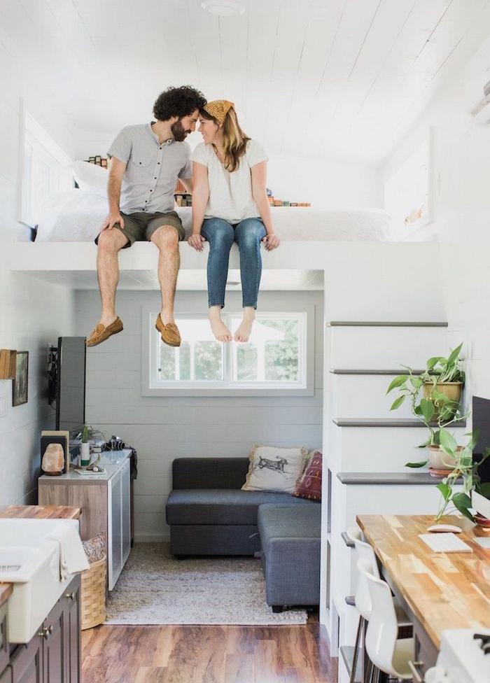 comment amenager une mezzaninee, idee amenagement studio lit matelas en hauteur, canapé d angle en face de meuble tv, bureau de travail et petite cuisine grise