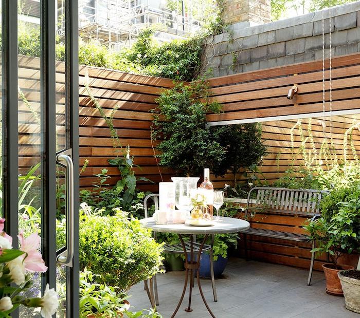 idee deco terrasse avec revetement en dalles de pierre, table ronde original, banc en metal, plantes vertes deco exterieur