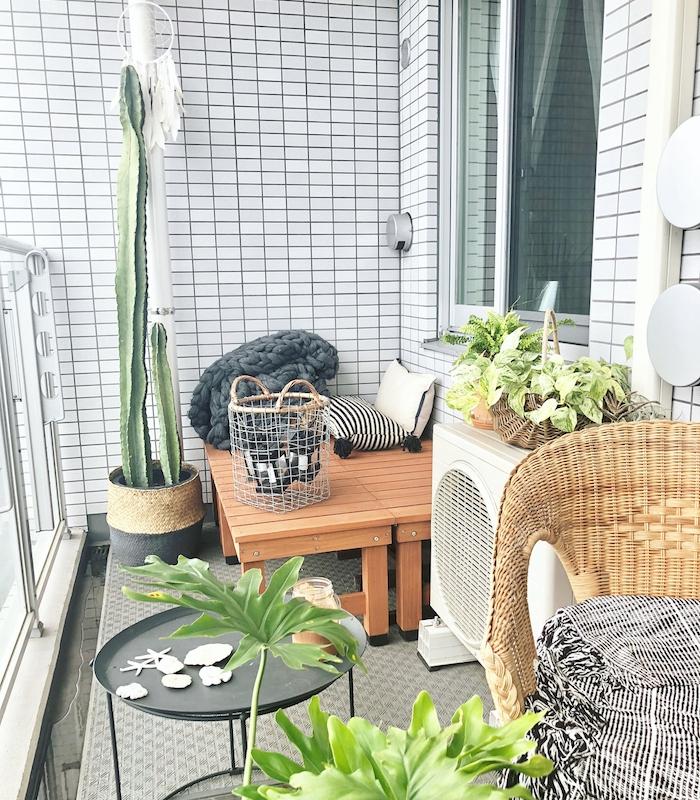 deco terrasse et balcon revêtu de carrelage blanc avec des bancs de bois et chaise de rotin, table basse noire, plantes exotiques d exterieur, tapis gris