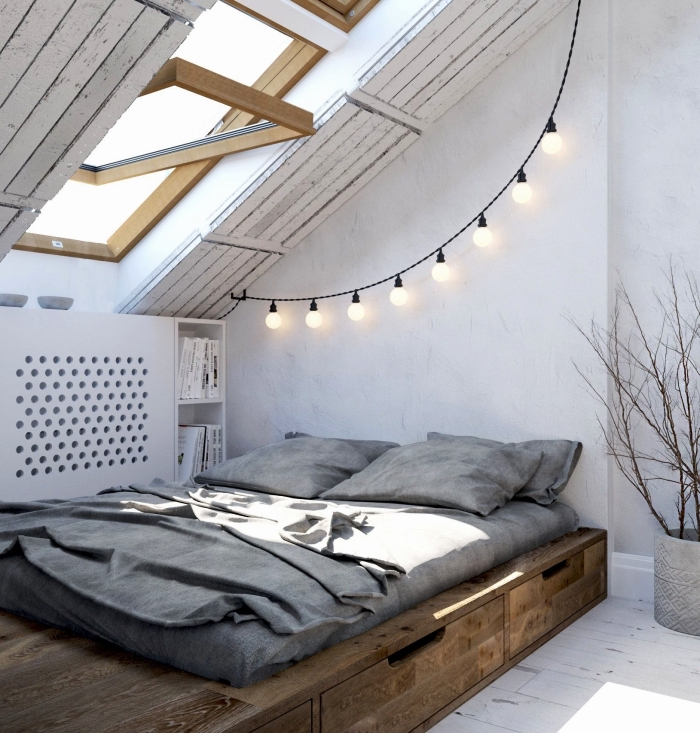 une chambre à coucher mansardée de style minimaliste avec lit bas à tiroirs intégrés et un meuble sous pente fonctionnel posé à côté