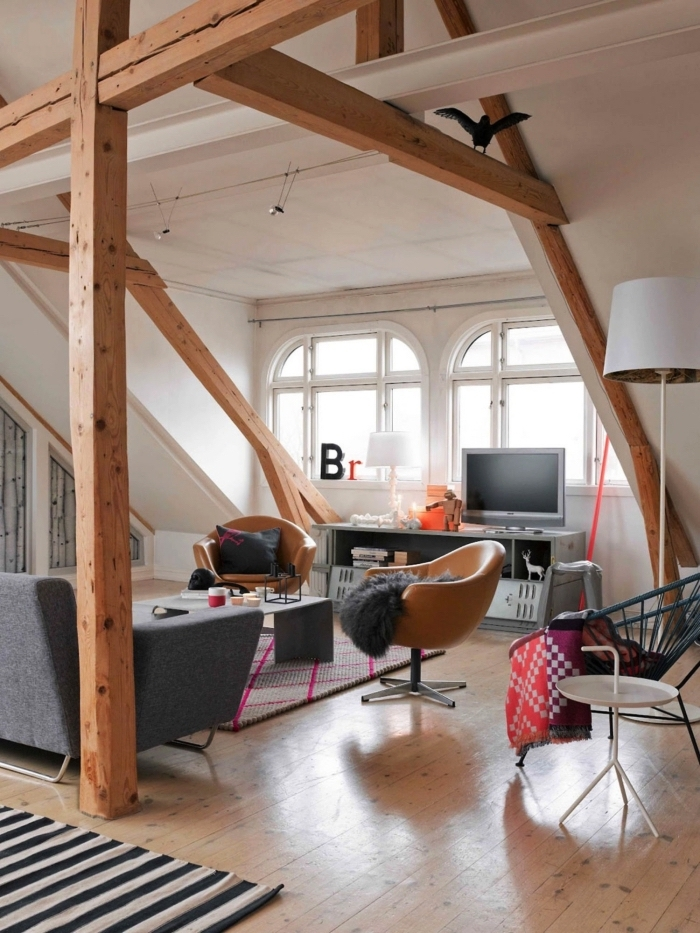 une chambre sous comble spacieuse de style vintage scandinave avec charpente apparente qui permet de structurer l'espace ouvert
