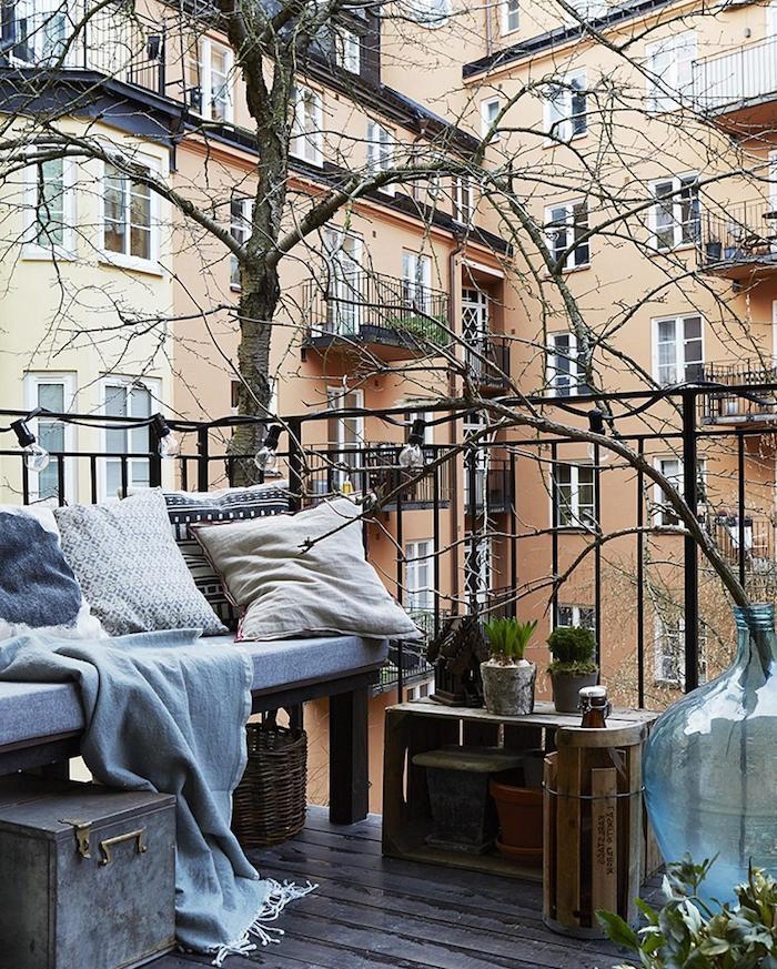 table et rangement cagette de vois deco, banquette de bois et coussin d assise gris avec des coussins decoratifs gris, plantes decoratives de balcon