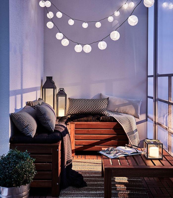 decoration balcon ambiance romantique avec guirlande boule exterieur, canapé d angle en bois, coussins noir et blanc, lanternes à bougies, tapis gris et blanc