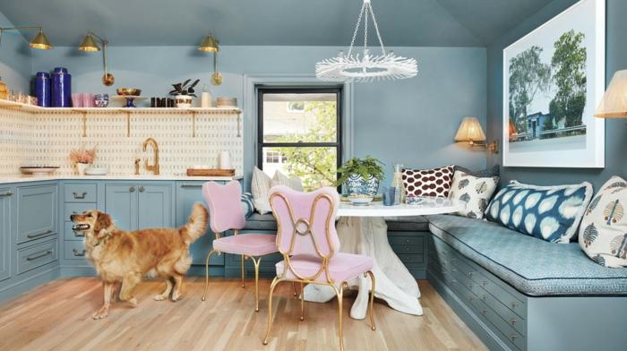 petite cuisine bleue et blanche, chaises roses, banquettes bleues, coussins déco, table ovale blanche, chandelier, kitchenette en angle