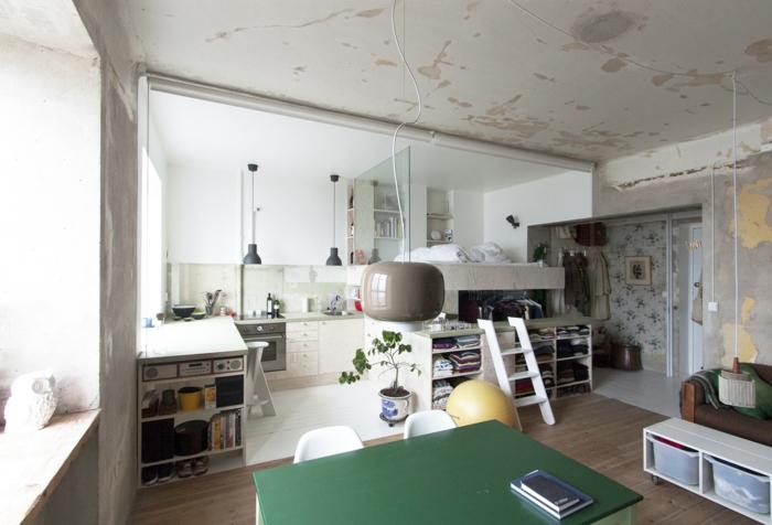 appartement loft industriel, petite cuisine moderne, sol en bois, plafond en béton, lit avec étagères