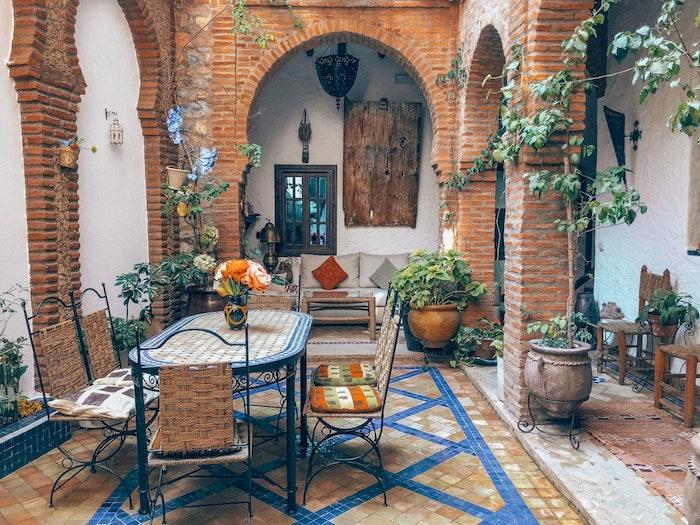 exemple de salon de jardin en en fer forgé constitué de table et chaises coin repas sur mosaique au sol, table et canapé gris, idee deco jardin style boheme chic