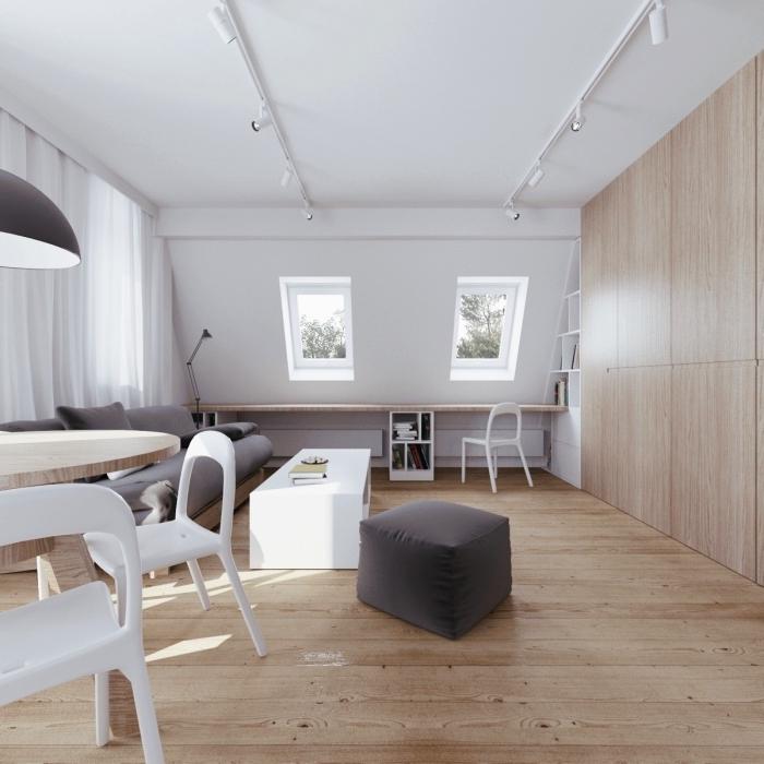 un salon sous combles de style scandinave en blanc,gris et bois avec meuble sous pente discret tout au long du mur, bureau sous pente composé d'une simple planche de bois