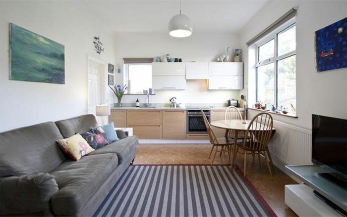 cuisine linéaire, tapis rayé, grand sofa gris, table ovale à rabats, meuble de tv blanc, tableaux peintures