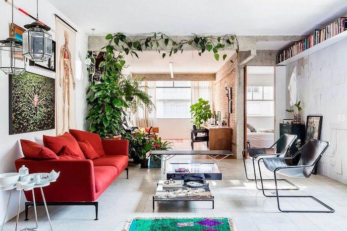 canapé rouge et chaises noires design rangés autour de deux tables basses dans un studio avec coin salon et bureau et coin nuit, deco de plantes vertes, décoration appartement