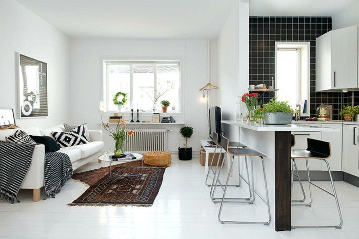 joli appartement studio, ilot de cuisine et chaises de bar, carreaux muraux noirs, tapis ethnique, sofa blanc, kitchenette ikea