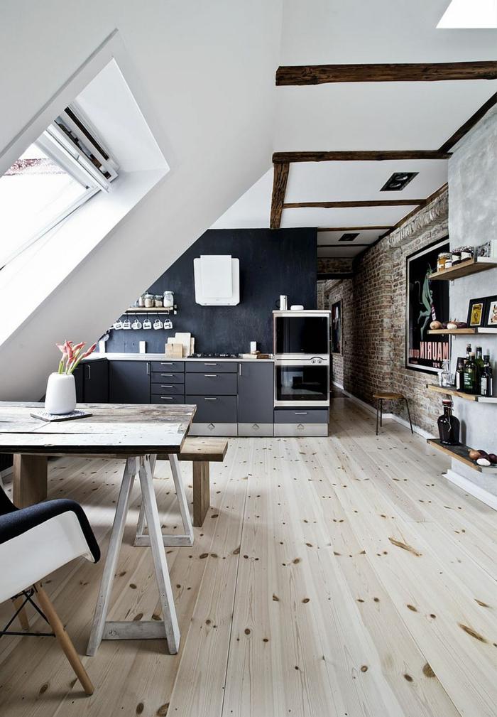 aménagement de kitchenette noire, studio mansardé, table et banquette en bois, mur en briques, étagères murales en bois