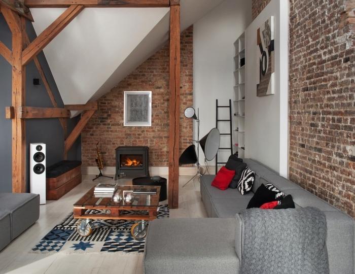 salon mansardé de style loft industriel avec grand canapé d'angle, table en palette et une cheminée de fonte, idée d'aménagement d'une chambre sous comble