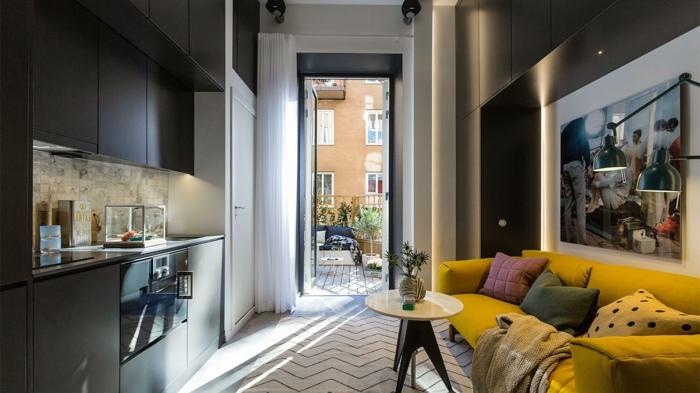 petite cuisine moderne dans un studio, sofa jaune, petite table ronde, éléctroménager, armoires de cuisine noires