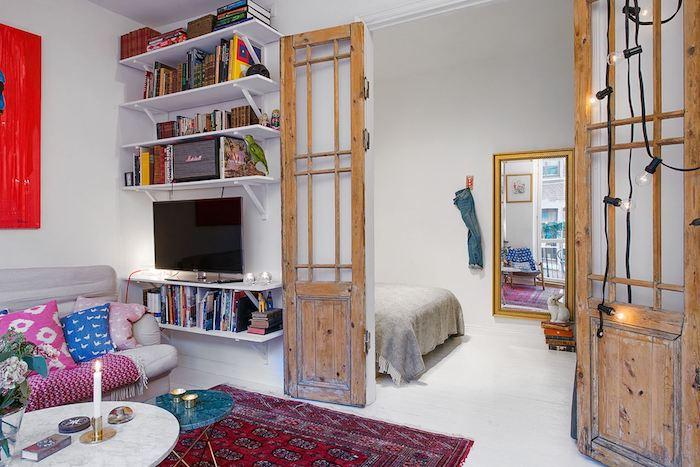 chambre à coucher ouverte sur un salon avec canapé gris décoré de coussins colorés, tapis oriental rouge, table basse marbre, portes bois volets anciens, deco studio boheme chic