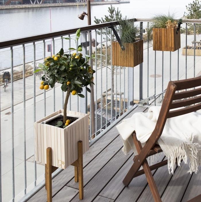 bacs à fleur accrochés sur un garde corps de balcon et pot à citronnier, chaise bois pliante sur balcon en bois