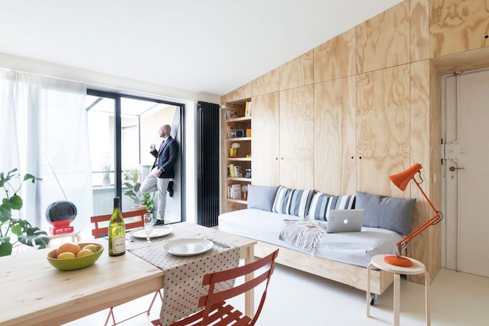 rangement et armoire en bois avec un canapé lit adossé, table à manger bois avec des chaises metalliques, décoration appartement petit