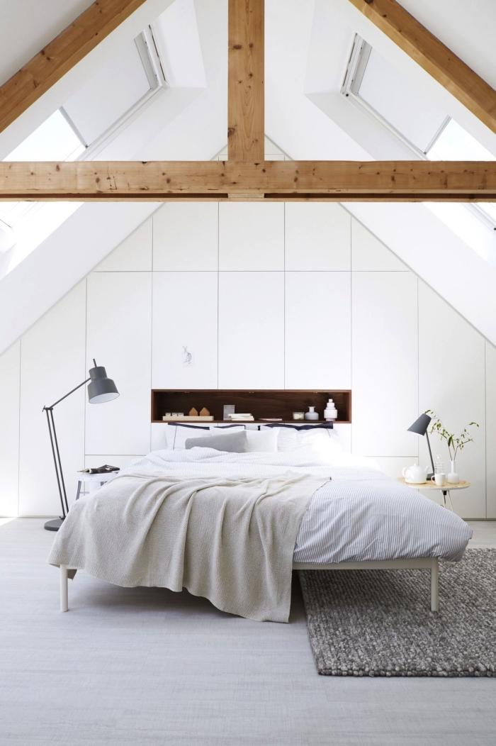 une armoire sous pente avec système de fermeture sans poignées au design épuré qui occupe le mur entier dans la chambre à coucher blanché aménagée sous les combles