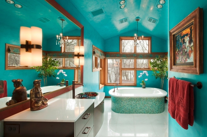 quelle peinture choisir pour salle de bain, exemple de salle de bain zen aux murs bleus avec décoration fleurs et statuette buddha