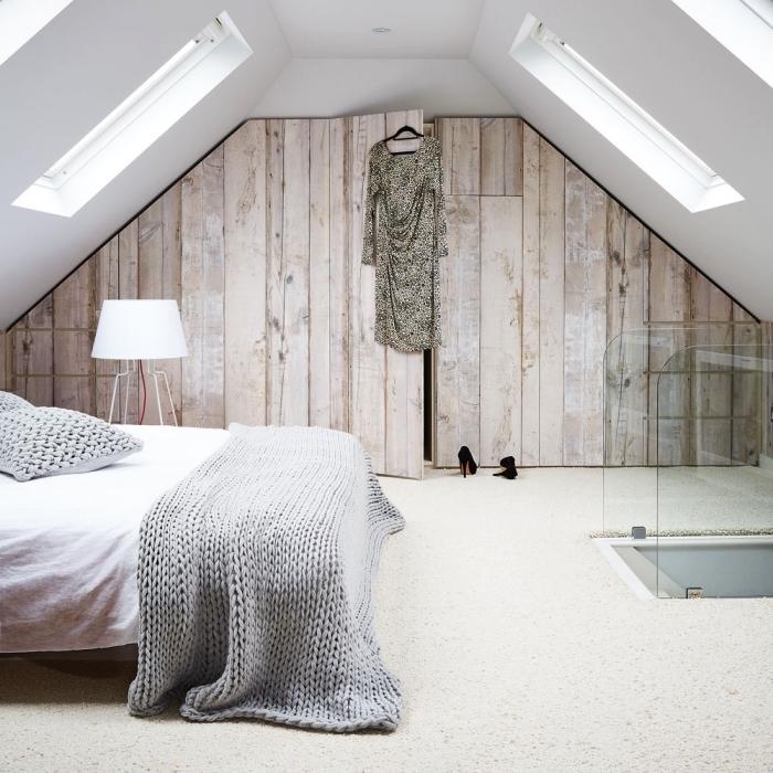 une chambre à coucher au design épuré aménagée sous les combles avec un dressing sous pente à portes imitation bois