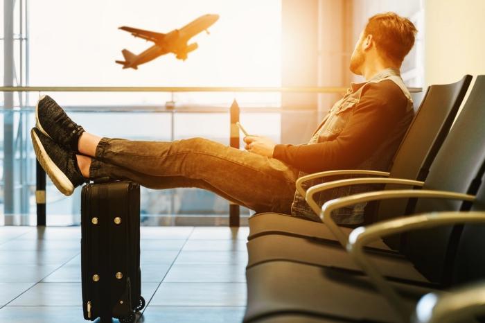 un homme assis confortablement dans la salle d'attente de l'aéroport regardant un avion qui décolle, astuces pour mieux organiser son voyage en avion