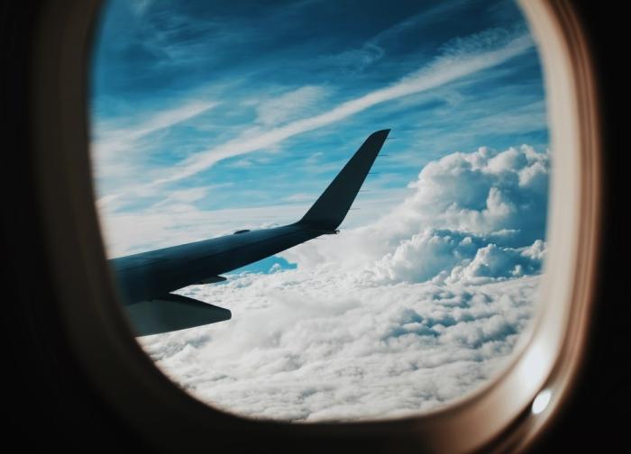 vue au travers le hublot d'un avion haut dans le ciel, mieux préparer son voyage en avion pour mieux profiter de ses vacances