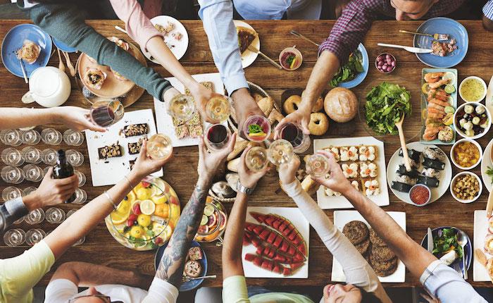 Chouette idée repas anniversaire avec des amis, mains qui se saluent avec vin blanc et rouge, idée de repas d anniversaire, bol de sangria, saumon dans un plat, salade dans un autre