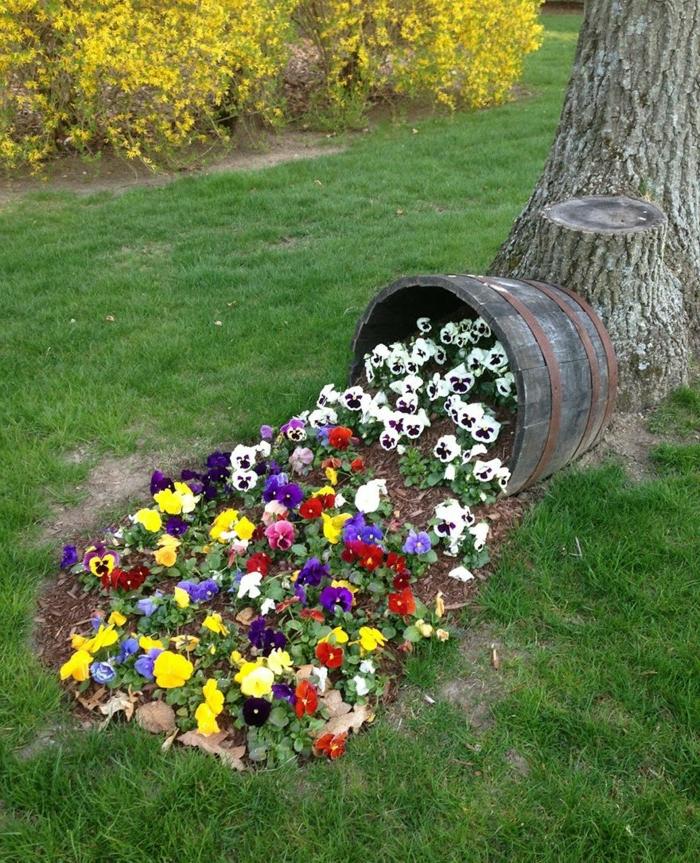 tonneau en bois et fleurs renversées, pelouse verte, haie de baies fleuries, decoration exterieur