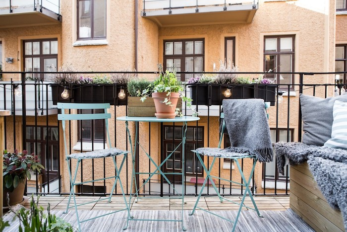 bacs à fleurs suspendus sur le garde corps d un balcon, idée comment aménager son balcon avec chaises et table en metal, tapis gris, banc bois couverte de coussins et plaid moelleux