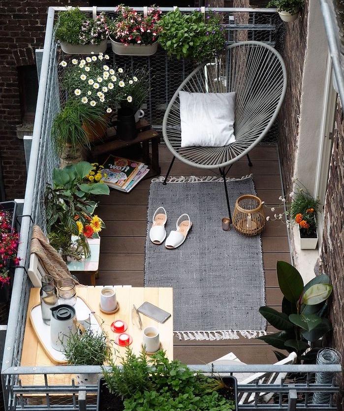 aménagement petit balcon fleuri avec chaise design, tapis gris, plantes de balcon fleuries, petite table balcon suspendue d angle