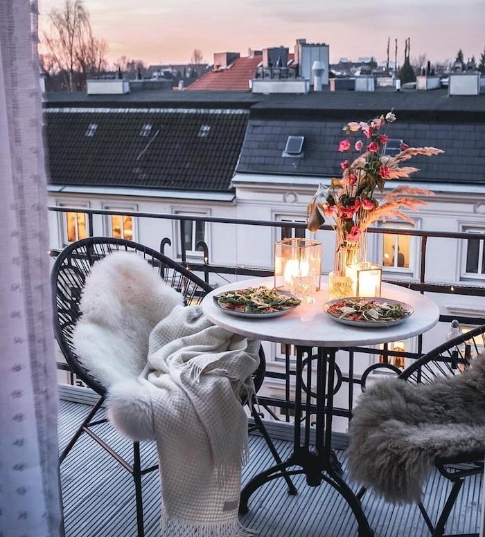 amenagement balcon avec des chaises fer forgé et table avec plateau marbre, deco bougies et vase de fleurs, belle vue, deco cocooning