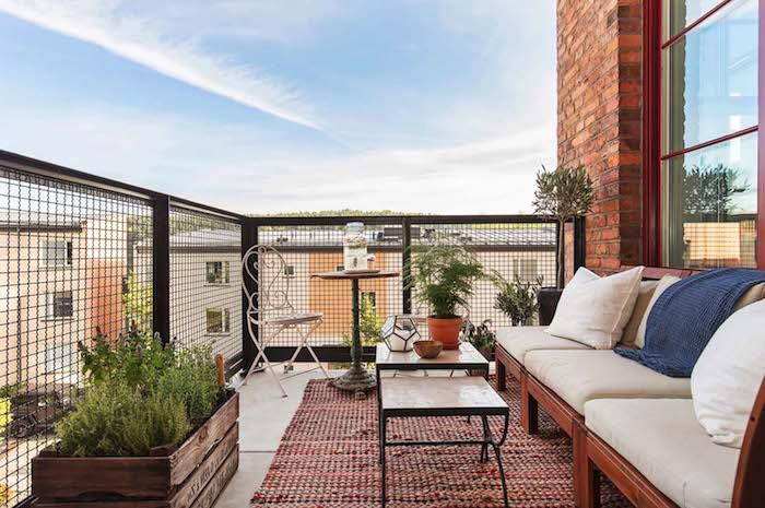 petit salon de balcon avec canapé bois avec coussins d assise gris, tables basses gigognes, tapis grosses mailles, bac à herbes