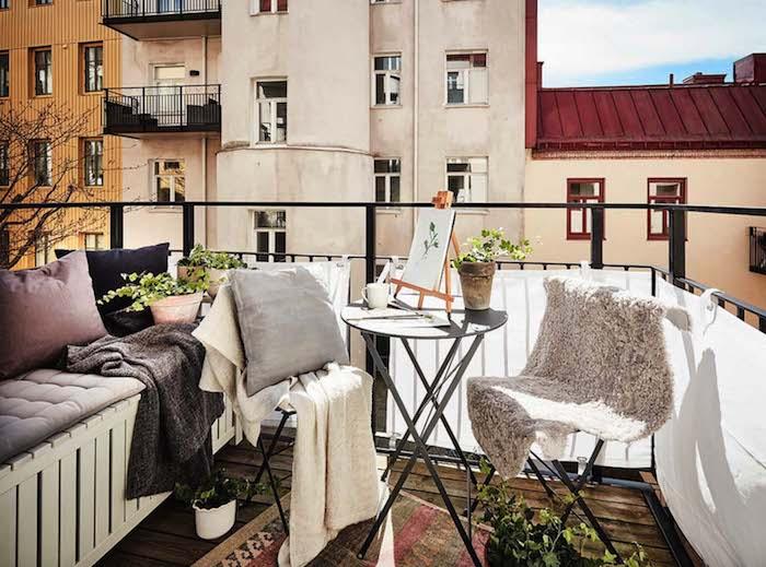 décoration balcon d'appartement avec une brise vue en toile blanche sur le garde corps, table pliante ronde grise, canapé bois avec coussins d assise gris, coussins décoratifs, tapis oriental