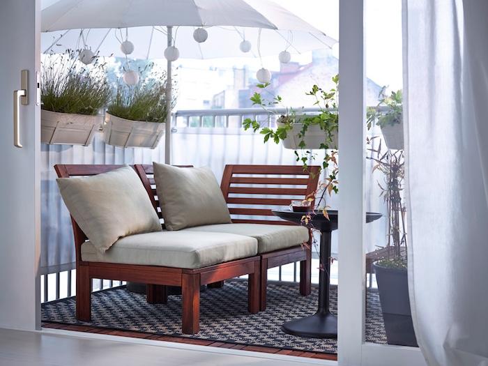 brise vue balcon en toile blanche, parasol blanc pour ombrage, canapé en bois, table basse ronde et tapis noir et gris, bas à fleurs suspendus