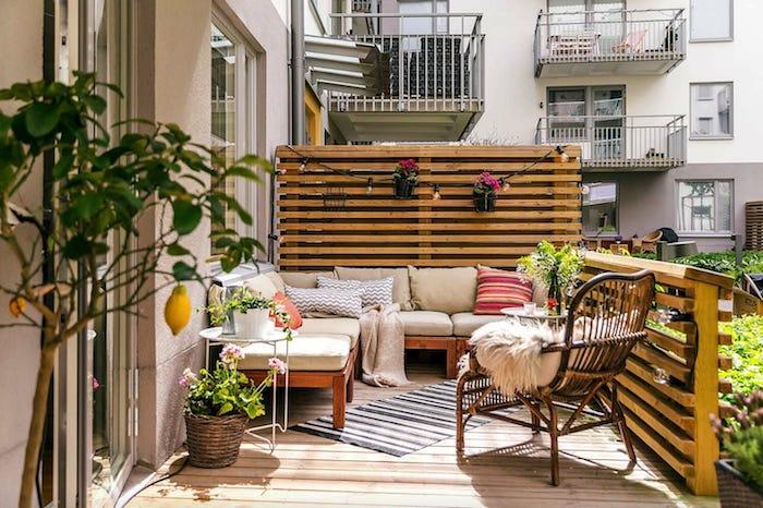 brise vue de balcon et mur végétal extérieur en palette de bois avec guirlande ampoules, canapé d angle de bois et chaise bois avec plaid cocoon, revetement sol bois
