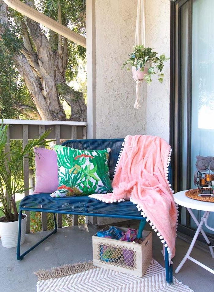 pot macramé suspendu, banc en métal bleu et coussin motif tropical, tapis beige et blanc, table de service pliante, bac de rangement sur balcon boheme