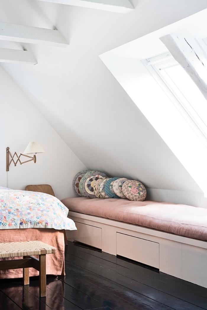 une chambre à coucher mansardée avec plancher en bois foncé et banquette sous fenêtre aménagée sous pente