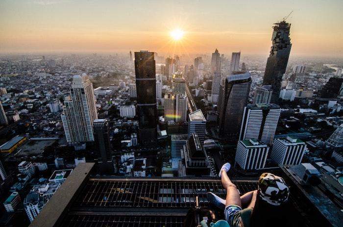 Paysage mégapole au coucher de soleil, femme qui regarde la belle vue, paysage magnifique, beau paysage urbain, motivation de voyager