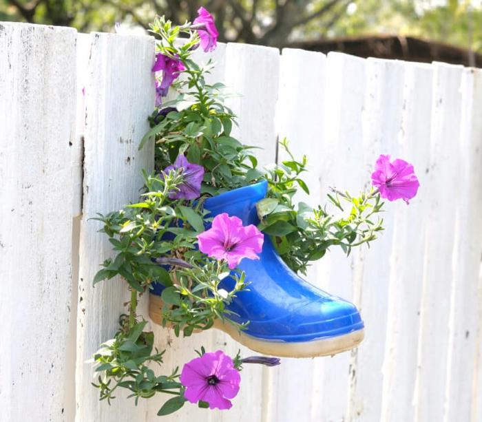 deco recup avec vieille botte peinte bleue accrochée à la palissade blanche, pétunias plantés