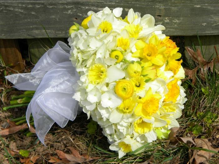 bouquet de mariée de jonquilles, ruban blanc satiné, bouquet mariage jaune posé sur l'herbe