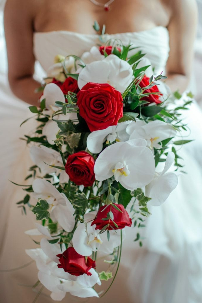 bouquet mariage cascade, callas blancs, roses rouges, feuillage vert, robe bustier blanche, collier