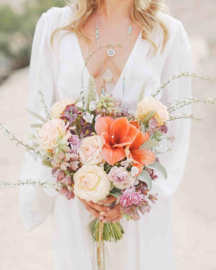jolie composition florale mariage, lys orange, roses couleur crème, fleurs mauves, décolleté triangle et bijux bohèmes