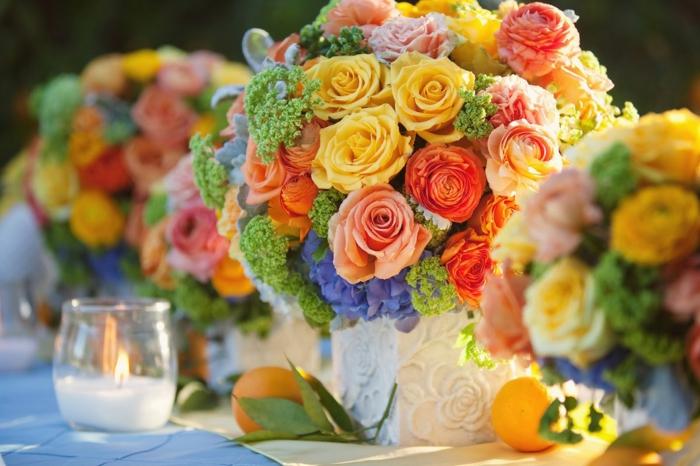 centre de table fleur pour mariage, table à nappe bleue, bouquets de roses oranges et jaunes