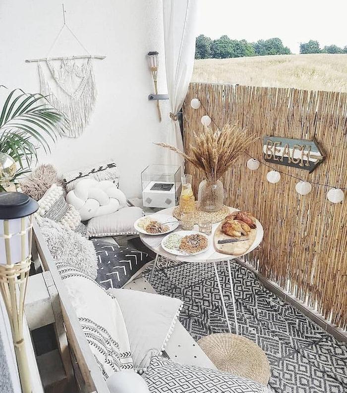 idee deco scandinave de balcon cosy monochrome avec brise vue osier, tapis noir et blanc, table blanche ronde, canapé décoré de coussins hygge scandinaves, deco murale macramé